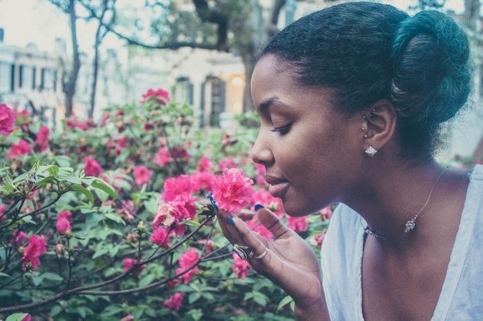 black girl smelling flowers