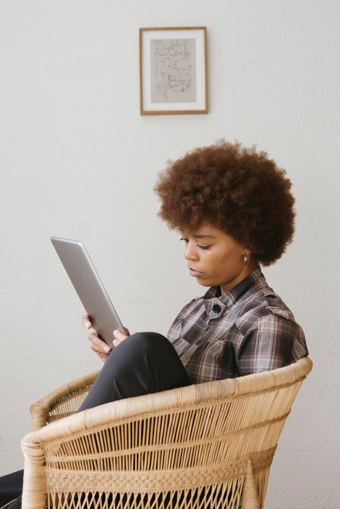 black girl sitting in chair with laptop